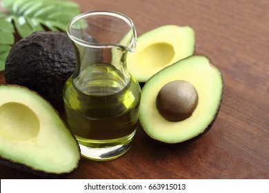 Three fresh avocado and avocado oil on wooden table/ Avocado and avocado oil