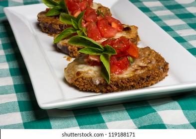 Three fresh bruschetta appetizers on white plate with basil