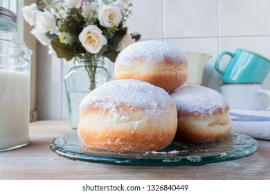 Three fresh doughnuts on a glass plate with coffee cups, flowers and milk bottle in background