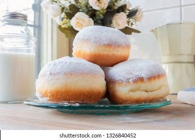 Three fresh doughnuts on a glass plate with moka pot, flowers and milk bottle in background