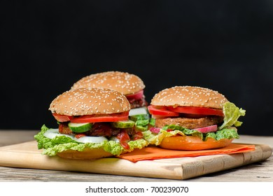 Three fresh homemade Burger with beef cutlet and vegetables on wooden table. Black background.