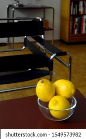 Three fresh lemons in a glass bowl on table, focus on foreground, room interior with club chair and furniture blurred in background