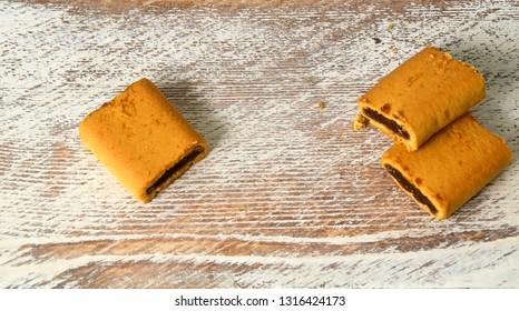Three fresh organic fig bar cookies on rustic wooden background.