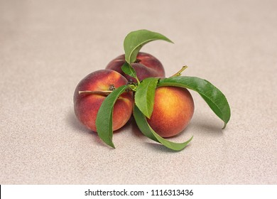 Three fresh peach fruits with leaves