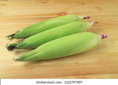 Three fresh purple corns with bright green husks and silks isolated on wooden background
