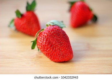 Three fresh strawberries photographed with a very shallow DOF with all the detail on the up front strawberry so it stands out the most.