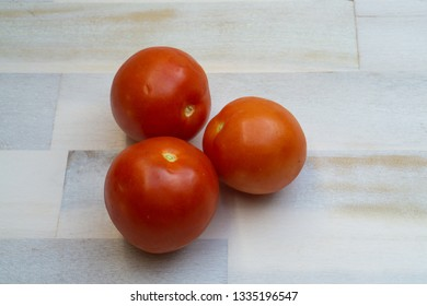 Three fresh tomatoes on wooden background