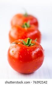 Three fresh tomatoes in a row