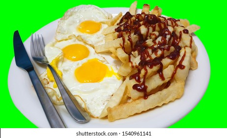 Three fried eggs, chips, french fries with brown sauce on a white plate on green background
