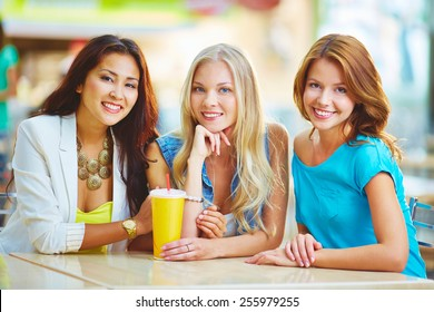 Three friendly girls having drink in cafe