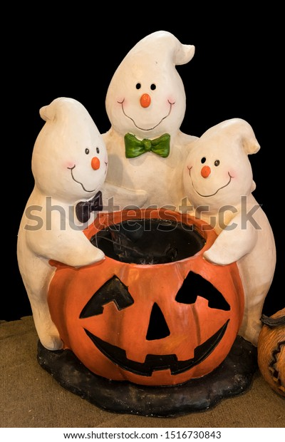 Three Friendly, Happy Smiling Ghosts Standing around a Pumpkin for Halloween.
