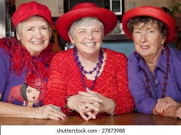 Three friendly senior women wearing red hats