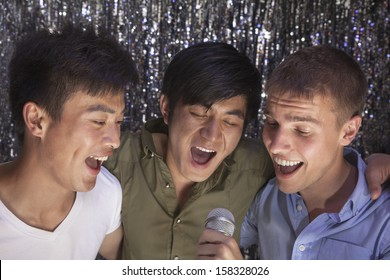 Three friends with arm around each other holding microphone and singing