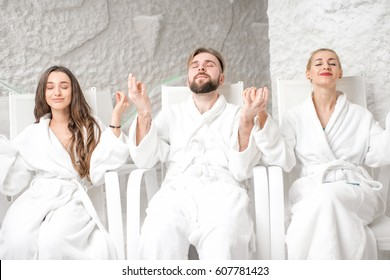 Three friends in bathrobes meditating in the salt room