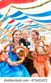 Three friends in beer tent at Dult or Oktoberfest holding giant pretzels up in the air