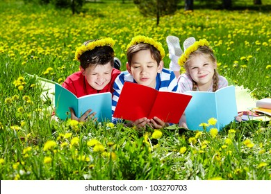 Three friends in dandelion wreaths reading on the lawn