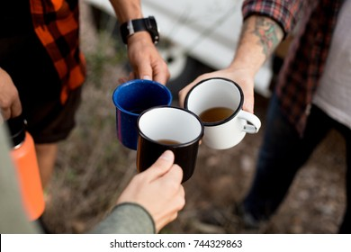 Three friends drink coffee or tea from hiking metal mugs or cups, hipsters with tattoos on adventure trip around europe, stop for rest or break to enjoy time together, hiking essentials