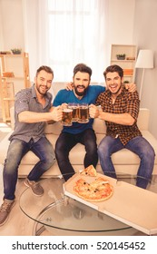 Three friends drinking beer and eating pizza while watching football