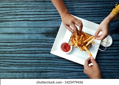 Three Friends Eating French Potato Fries, Serve on Metal Mesh Flying Sieve with Two Dipping Sauce. Lay on Wooden Table. High Angle Top View Shot
