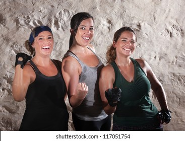 Three friends flexing their muscles in boot camp style workout