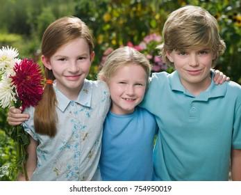 Three friends in a garden smiling