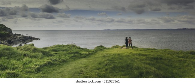 Three friends gather over the edge of a cliff looking out to the sea near Galley Head Ireland