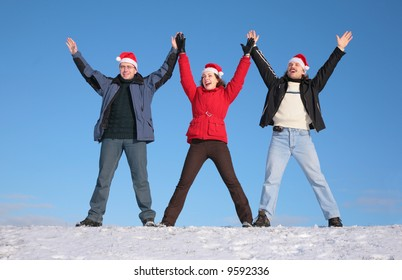 three friends greetings on snow  in santa claus hats