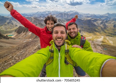 Three friends are a group of hikers having fun and making selfie on the top of the mountain. Happy faces of people who reached success and a amazing peaks landscape