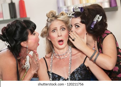 Three friends in hair salon whispering to each other