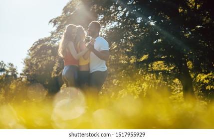 Three friends having fun dancing kizomba on a meadow in afternoon
