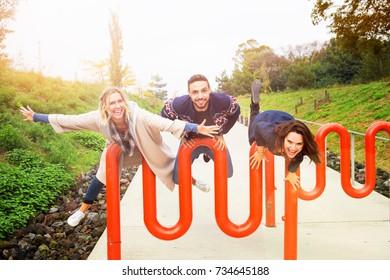 three friends having fun outdoors and enjoying the sun in autumn