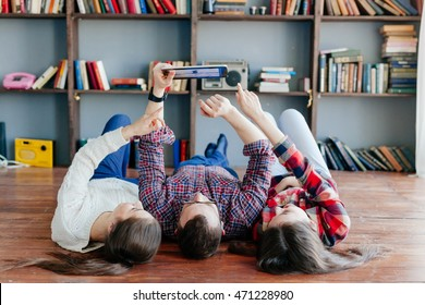 Three friends holding tablet at the floor