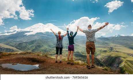 Three friends joined hands and raised their hands up, enjoying the view of the mountains in the summer. Summer Vacations Outdoor Concept
