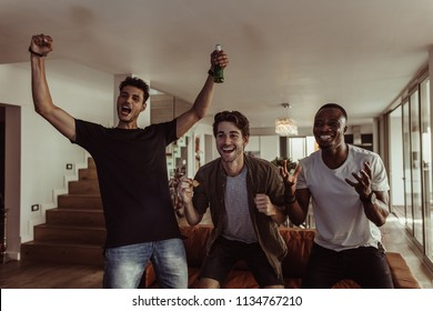 Three friends jumping in excitement holding beer bottles and snacks while watching television. Men having fun with drinks and snacks while watching television at home.