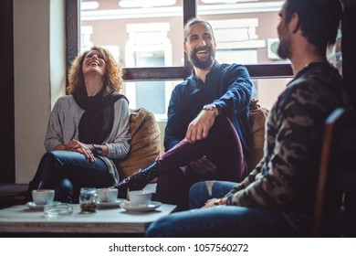 Three friends laughing in a cafe while drinking coffee