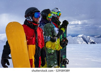 Three friends look forward snowboarders courageously stand in a row against the backdrop of Snowfall in the mountains