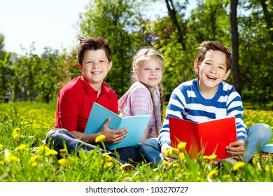 Three friends looking at camera while reading on the lawn
