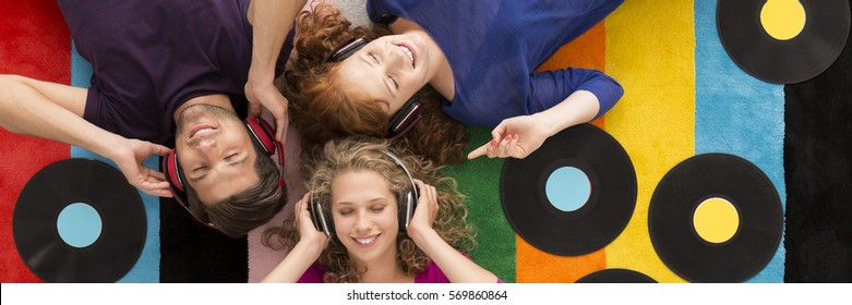 Three friends lying on the floor with closed eyes and listening to music through earphones