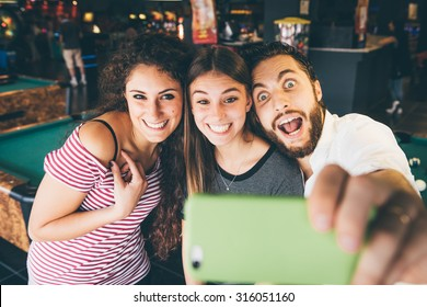 three friends make a selfie in playroom