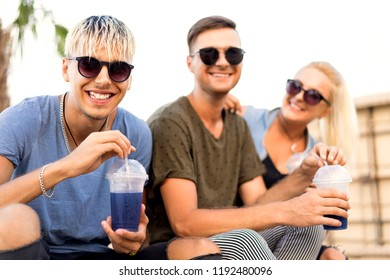 three friends on the beach spend fun while drinking cocktails at sun