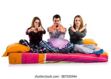 Three friends on a bed making stop sign