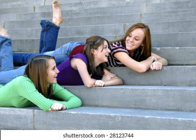 Three friends relax on dormitory steps.  They are smiling and chatting.  All are wearing jeans.