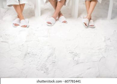 Three friends relaxing in the salt room. Close-up view on the legs with copy space