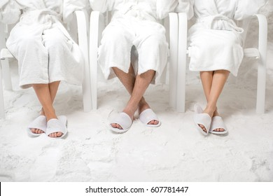 Three friends relaxing in the salt room. Close-up view on the legs and salt