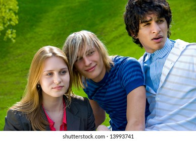 Three friends rest on a lawn in a park