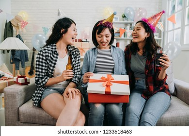 three friends sharing happy moments opening birthday present. young asian girl curiously looking inside gift box. beautiful ladies giving surprise and drinking beer love alcohol.