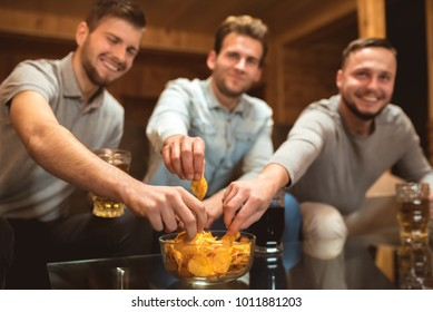 The three friends sit and eat chips