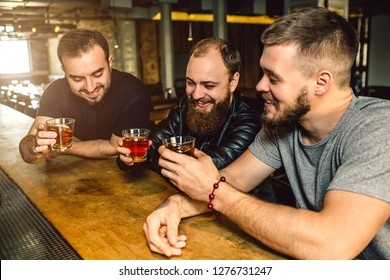 Three friends sit together at bar counter. They hold glasses of alcohol in hands. Men smile.