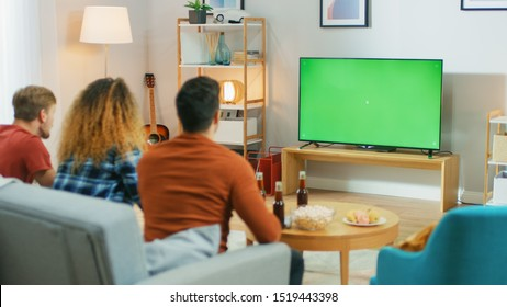 Three Friends Sitting on a Couch at Home, Watch Green Chroma Key Screen TV while Eating Snacks and Drinking Beverage. Young People Having Fun at Home.