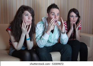 Three friends sitting on the couch in the living room and watching something scary on TV
